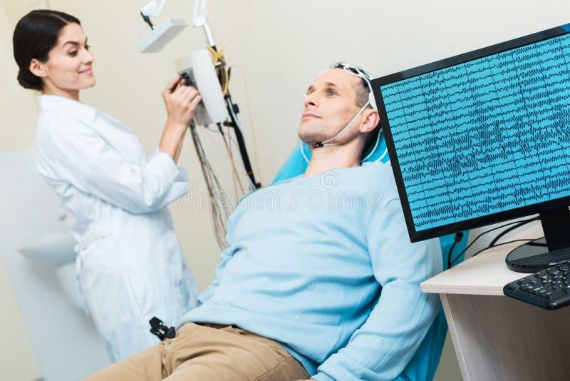 安排年轻的人他的脑波被记录在脑波记录仪期间 免版税库存照片