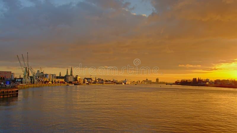 安特卫普都市风景在河Scheltdt的,有大教堂和其他塔的在朦胧的温暖的日落光 免版税库存照片