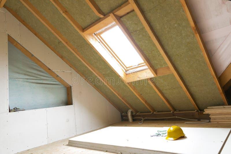 安置与岩石的顶楼建设中有双重斜坡屋顶的房屋的墙壁绝缘材料 库存图片