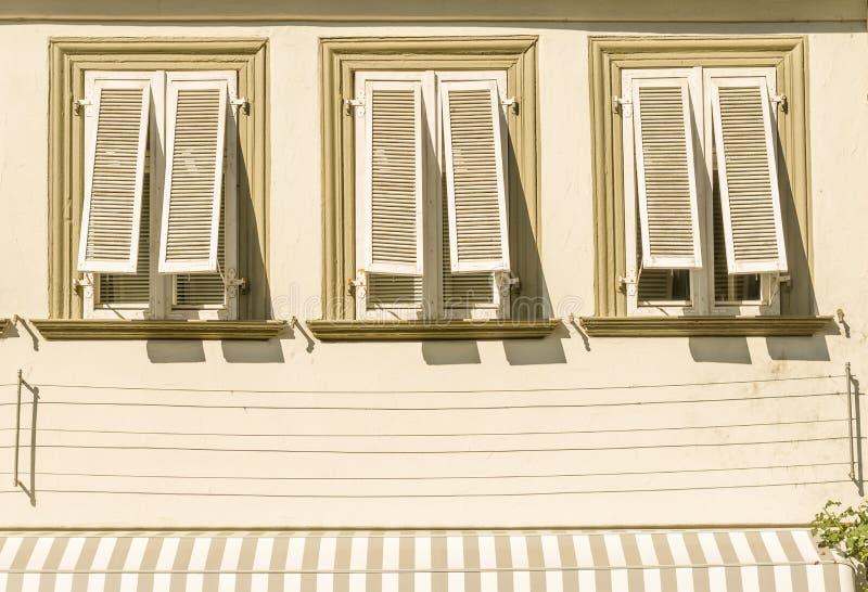 安置与灰泥3窗口和展开的木头快门aw的门面 免版税库存照片