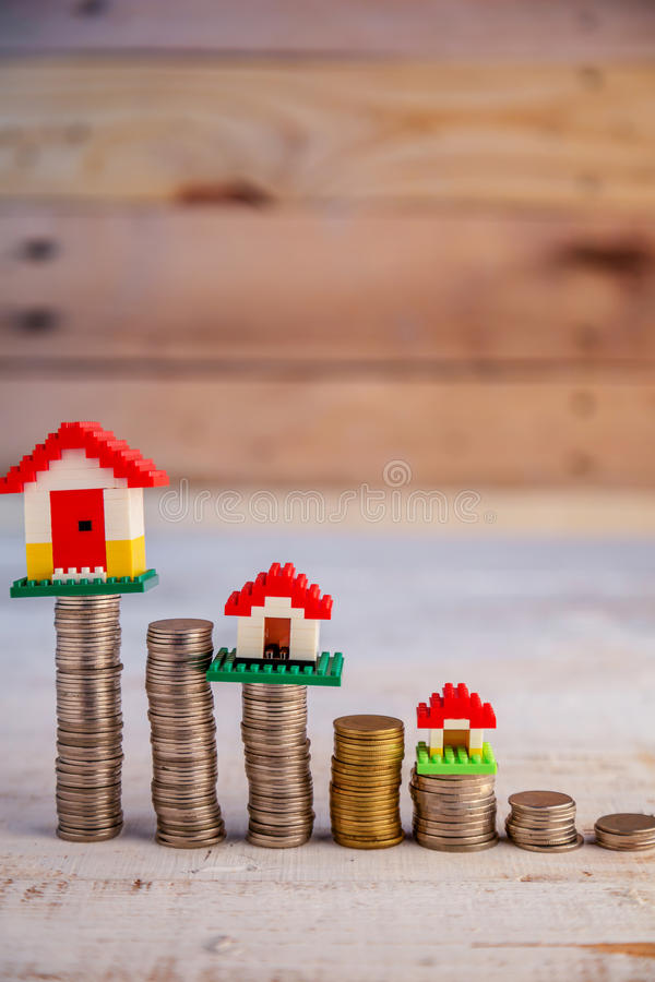 安置与被堆积的硬币的模型在木桌商业资产c 免版税库存照片