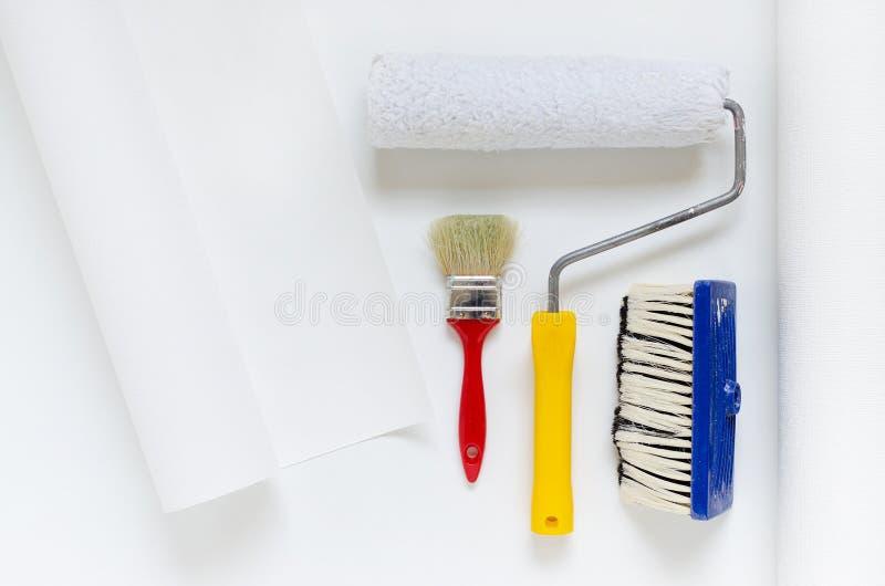 安置修理设备、白色墙纸卷与漆滚筒和刷子 免版税库存照片