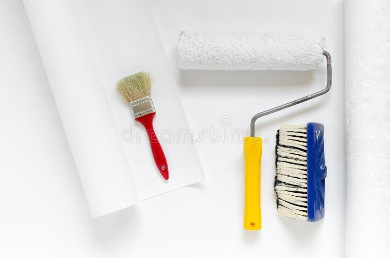 安置修理设备、白色墙纸卷与漆滚筒和刷子 免版税库存图片