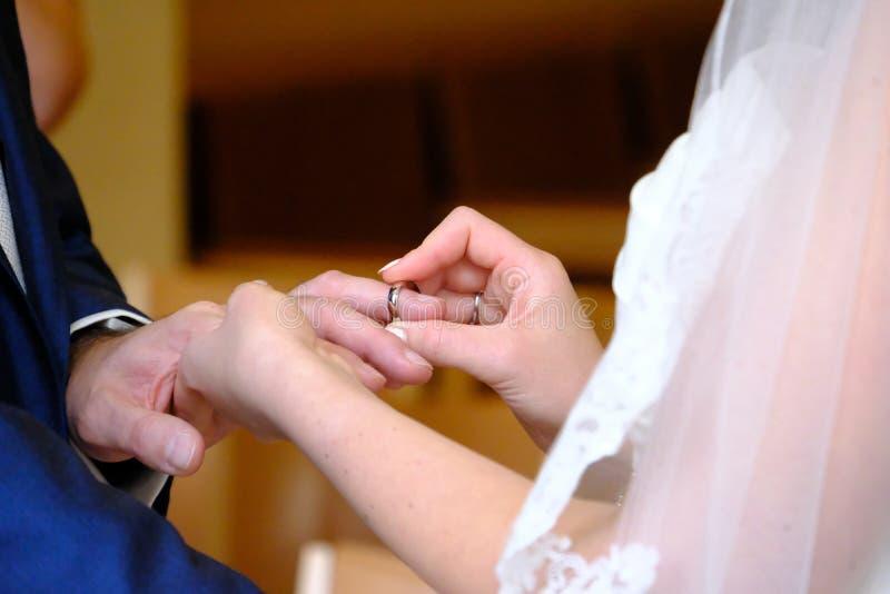 安置婚戒在新郎` s手指在民用婚礼 免版税库存照片