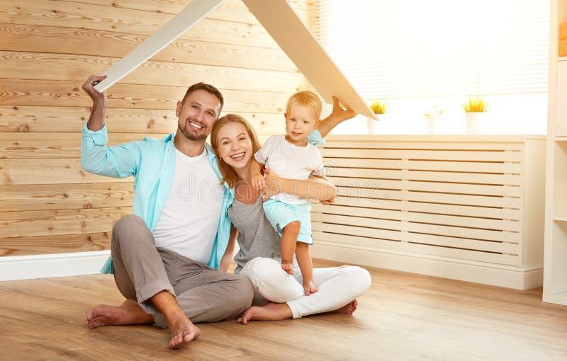 安置年轻家庭的概念 母亲父亲和孩子新的ho 免版税图库摄影