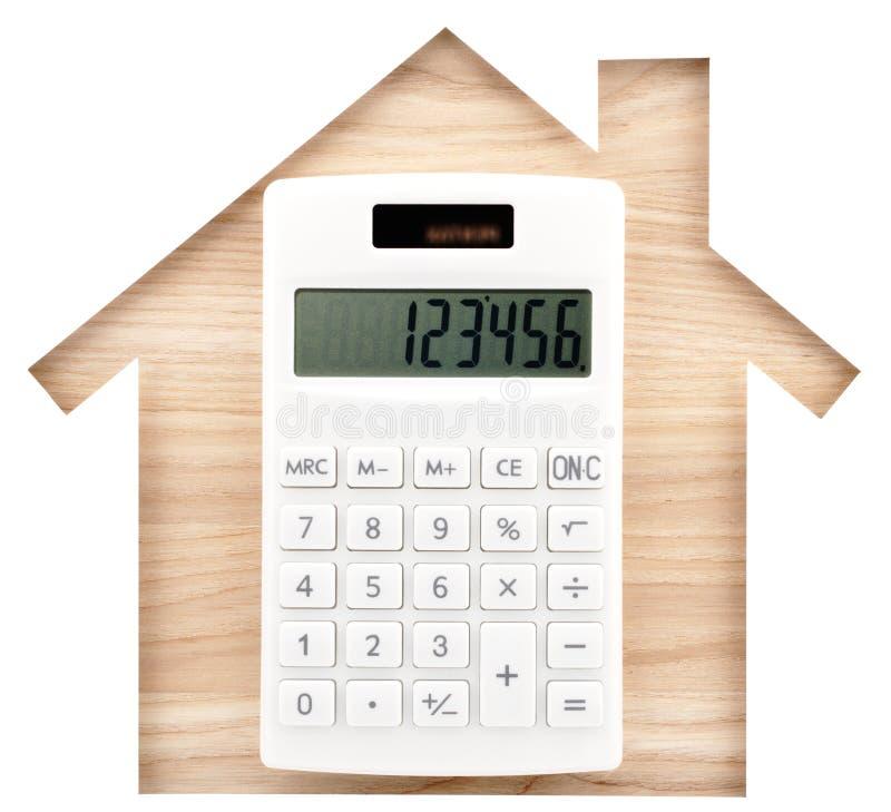 安置形状的纸保险开关和白色计算器在自然木头l 免版税库存照片