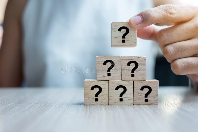 安置或拉扯问号的女实业家手?与木立方体块的词在大厦 常见问题解答频率要求 免版税图库摄影