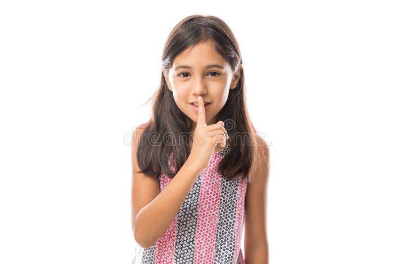 安置手指的女孩在要求的嘴唇嘘,安静,在白色的沈默 免版税库存图片
