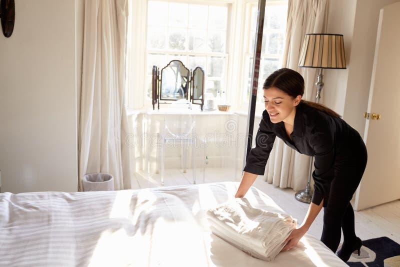 安置新鲜的亚麻布的女服务生对床在旅馆客房 库存照片