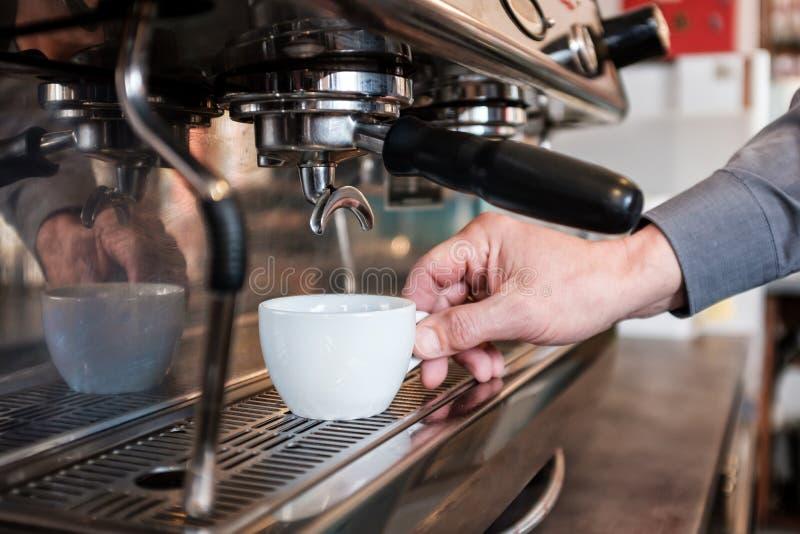安置杯子的Barista在咖啡机器对做新鲜的浓咖啡 免版税库存照片