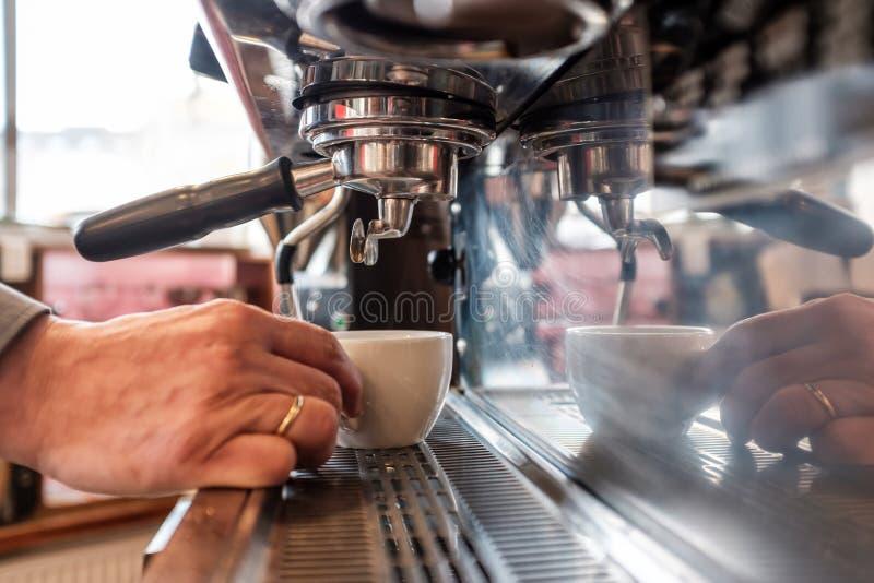安置杯子的Barista在咖啡机器对做新鲜的浓咖啡 库存图片