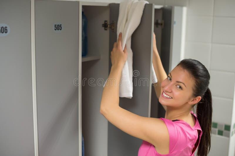 安置毛巾的妇女在衣物柜门 免版税库存照片