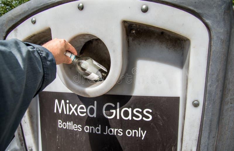 安置玻璃瓶子的人的胳膊入在U的瓶银行回收站 K 免版税图库摄影