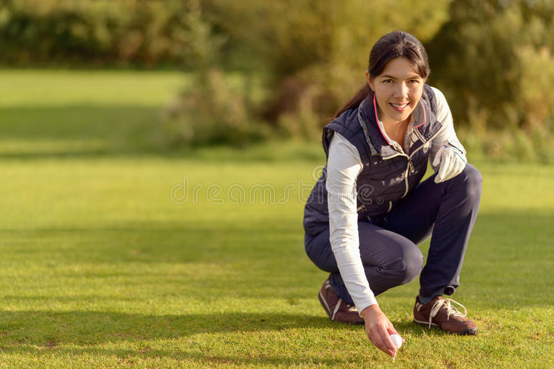 安置球的微笑的女性高尔夫球运动员在发球区域 库存图片