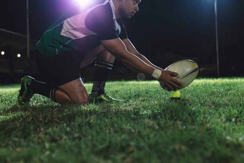 安置球的橄榄球球员在惩罚的发球区域 库存图片