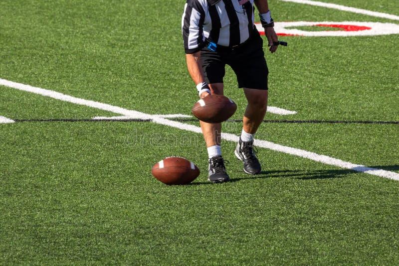 安置球的裁判员在橄榄球场 库存图片