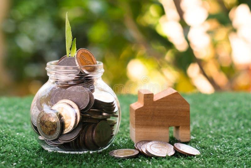 安置的金钱 木房子模型、硬币和钞票在玻璃瓶子有绿叶背景 库存图片