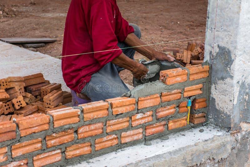 安置砖的建筑工人在修造的水泥 库存照片