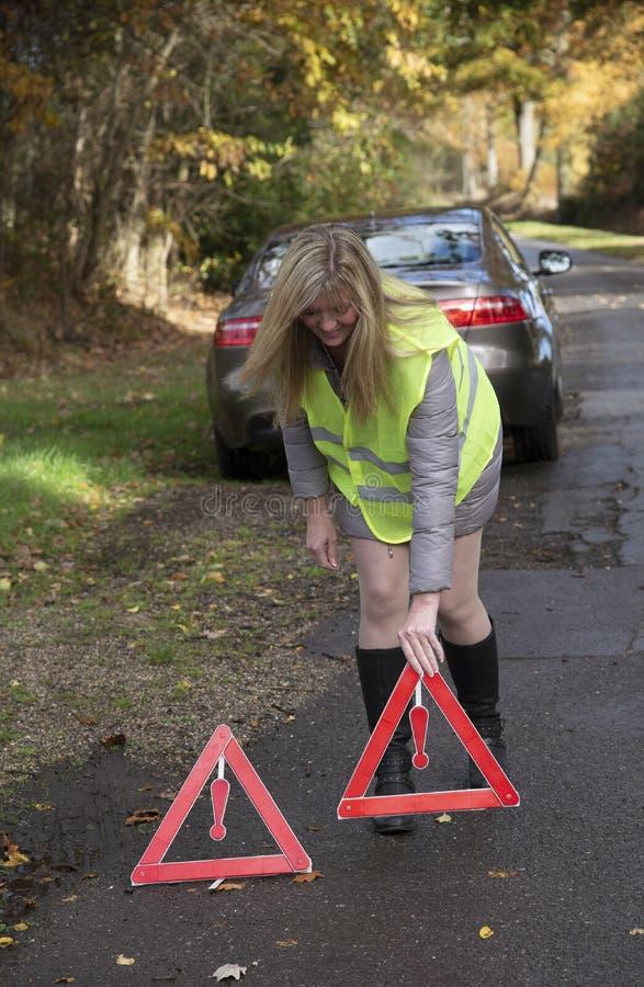 安置红色警告三角的女性驾驶人在路, 免版税库存图片