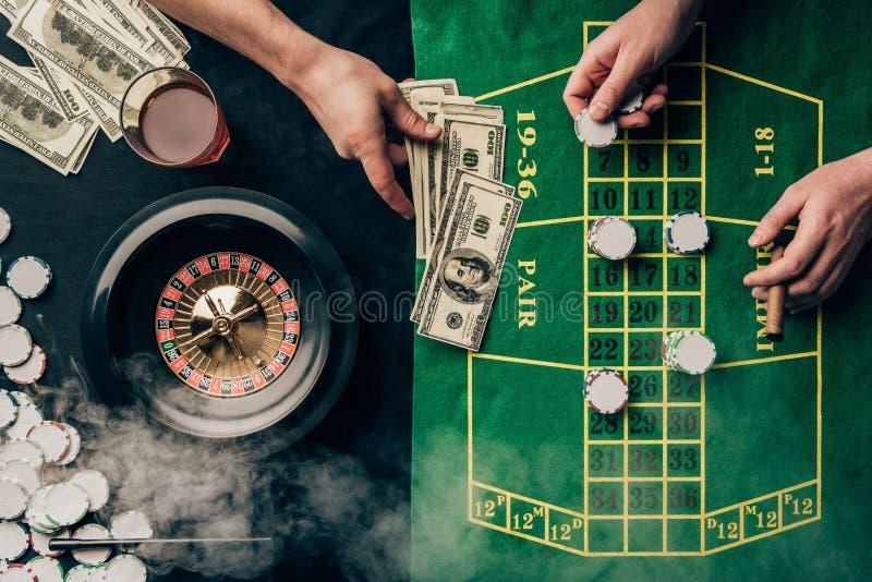 安置赌注的人在赌博娱乐场桌 库存图片