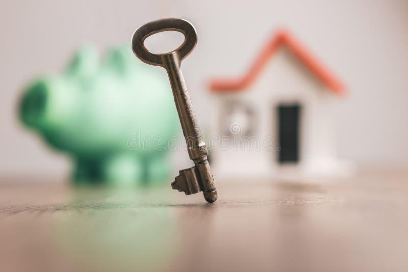 安置钥匙在堆硬币顶部在一张木桌顶部,与被弄脏的房子和存钱罐背景的:概念 免版税库存照片