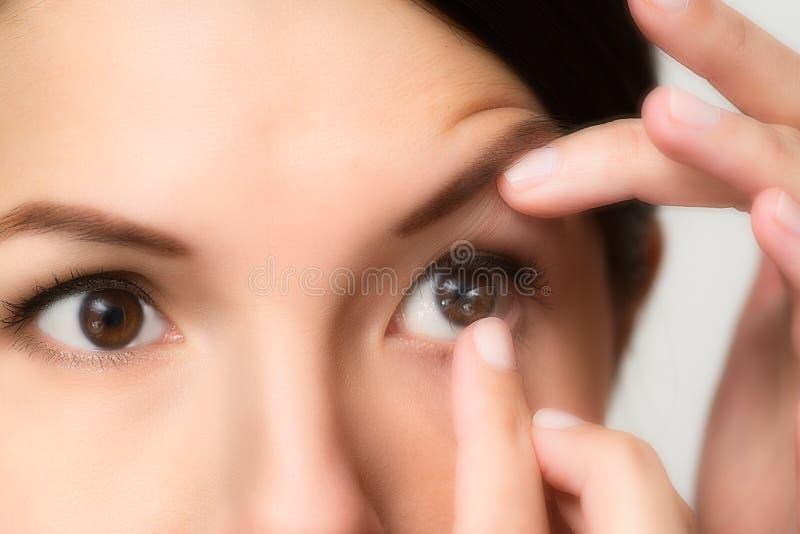 安置隐形眼镜的妇女在她的眼睛 免版税库存照片