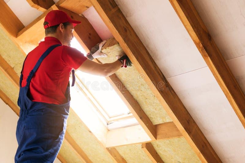 安置顶楼绝缘材料-安装羊毛的建筑工人 免版税图库摄影