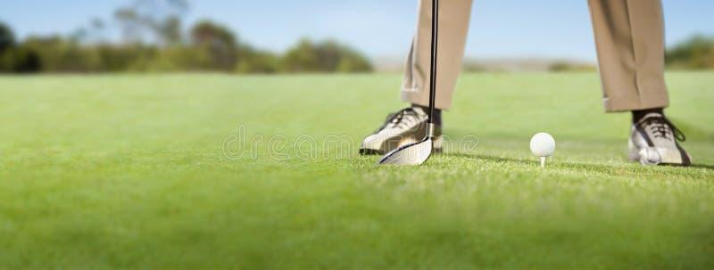 安置高尔夫球的高尔夫球运动员在发球区域 库存图片