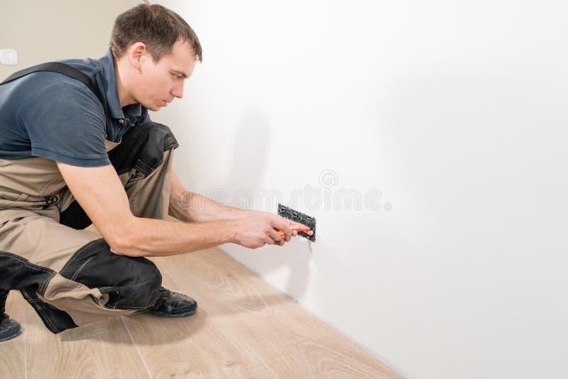 安装一个电子插口的一位年轻电工在一个新房 免版税库存图片