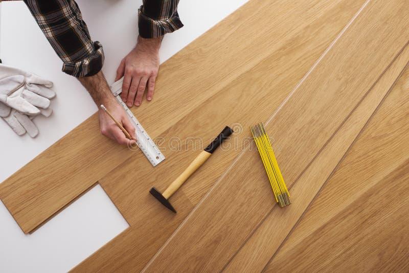 安装一块木地板的木匠 免版税库存照片