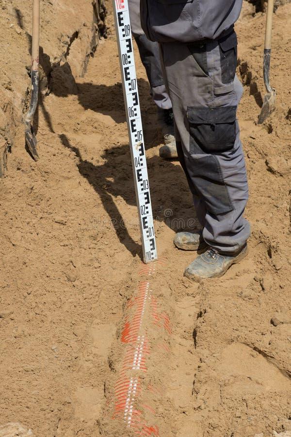 安装下水道的工作者在含沙沟槽 免版税库存图片