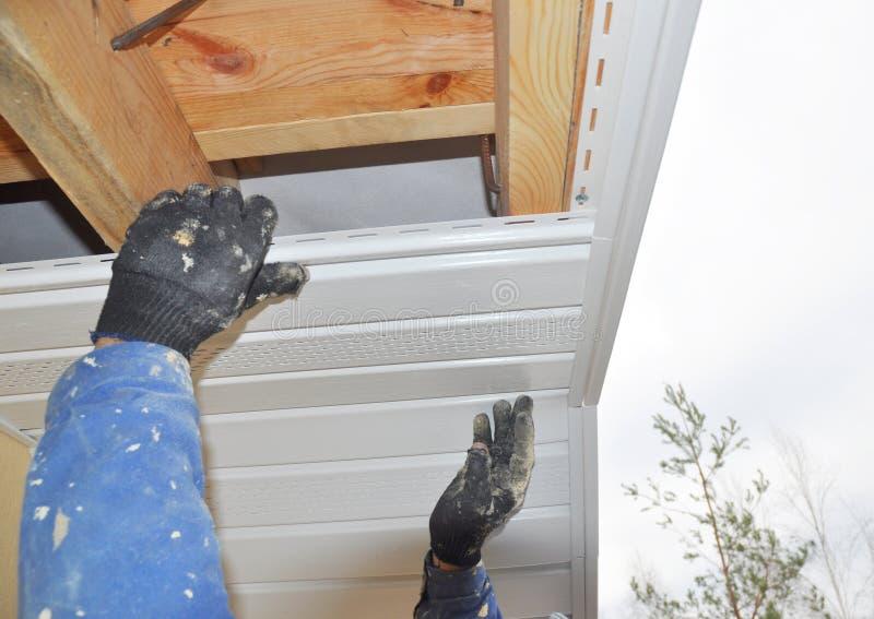 安装下端背面的承包商在房子屋顶建筑上 库存图片
