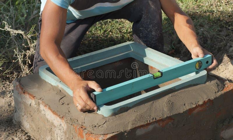 安装下水道出入孔 免版税库存图片