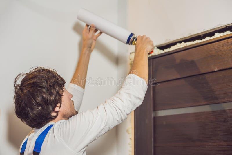 安装与架置泡沫的年轻杂物工门在屋子里 库存图片