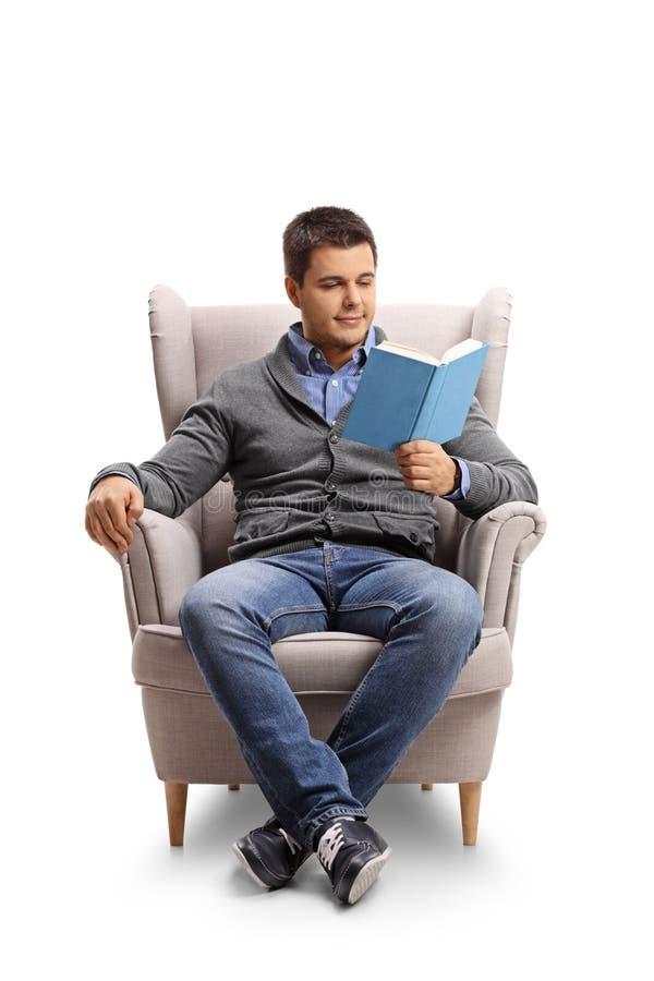 安装了读书的年轻人在扶手椅子 图库摄影