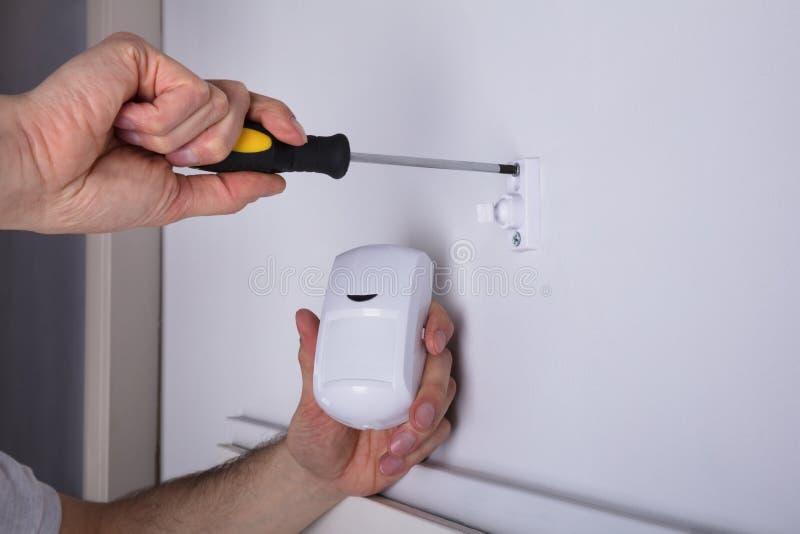 安装保安系统门传感器的电工在墙壁 免版税库存图片