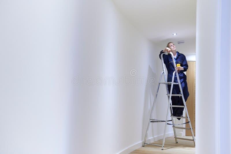 安装光的女性电工在天花板 免版税库存图片