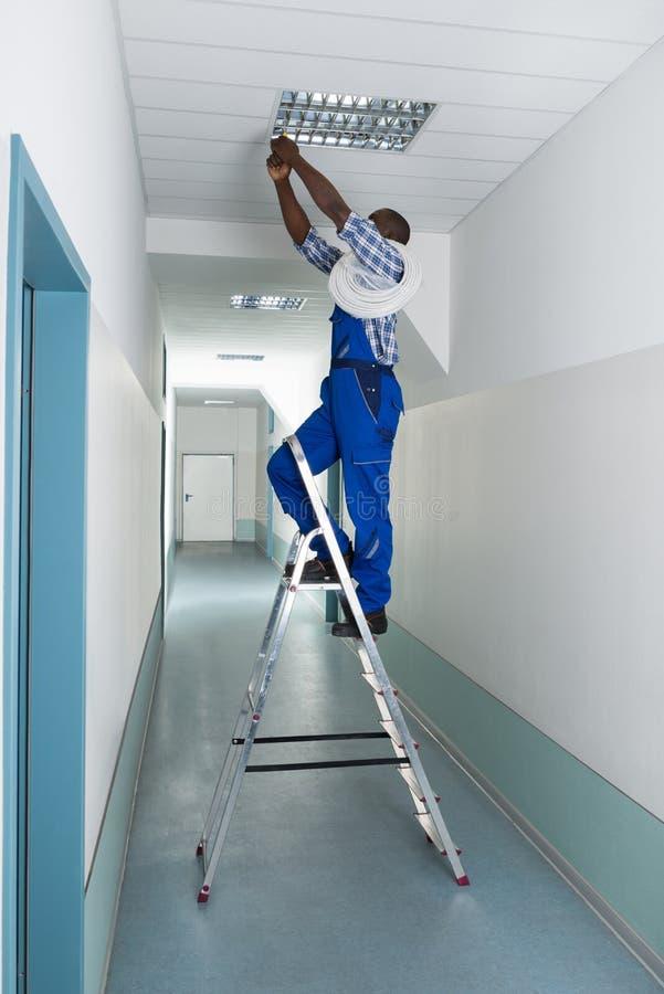 安装光的电工在天花板 库存照片