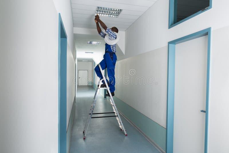 安装光的电工在天花板 图库摄影