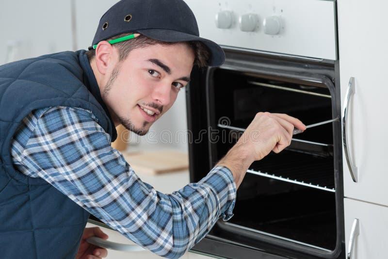 安装全新的烤箱的总体的年轻安装工在厨房 库存照片