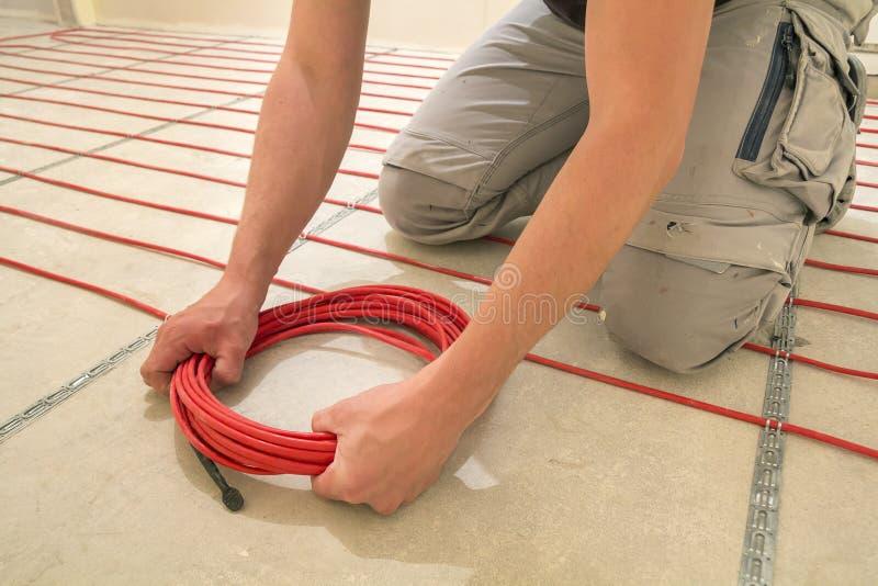 安装加热的红色电缆导线的电工在水泥地板在未完成的屋子里 整修和建筑, 图库摄影
