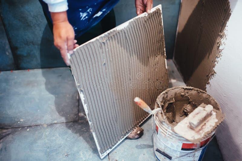 安装卫生间陶瓷地垫的工作者,增加与梳子修平刀的灵活的水泥胶粘剂 免版税库存照片
