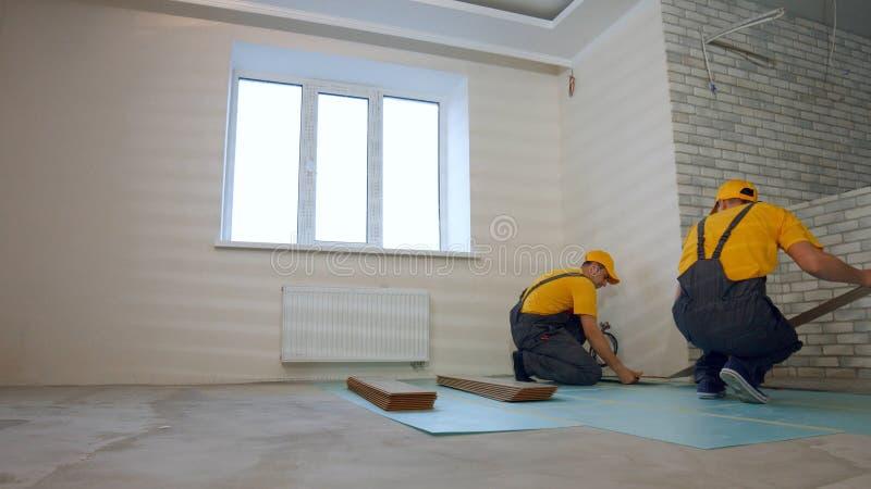 安装台面厚木板的制服的男性工作者 免版税图库摄影