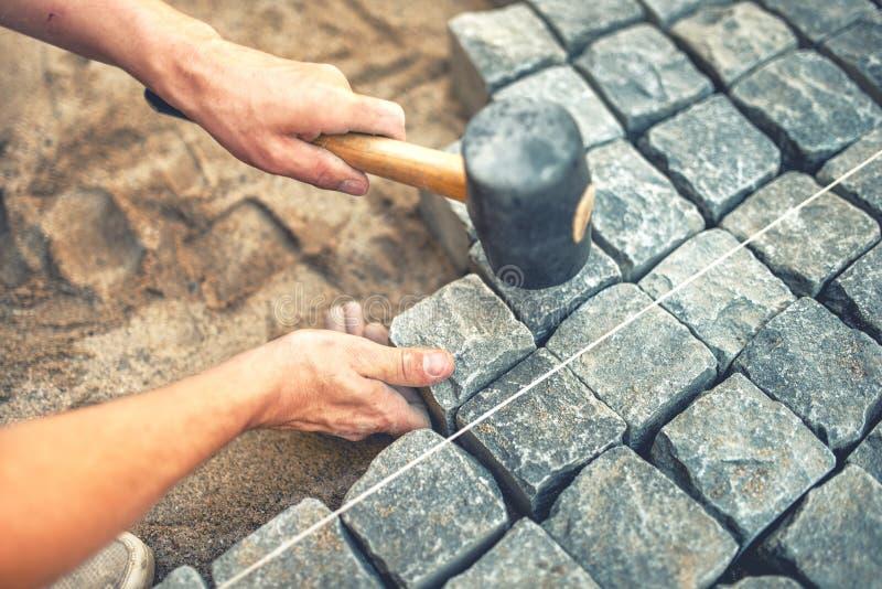 安装和放置路面石头的建筑工人特写镜头在大阳台、路或者边路 使用石头和橡胶的工作者 免版税库存图片