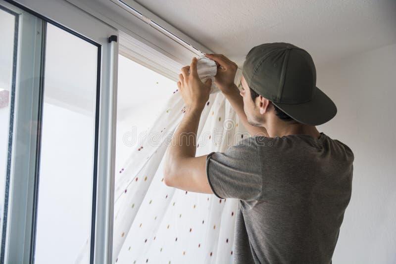 安装在窗口的年轻人帷幕 免版税图库摄影