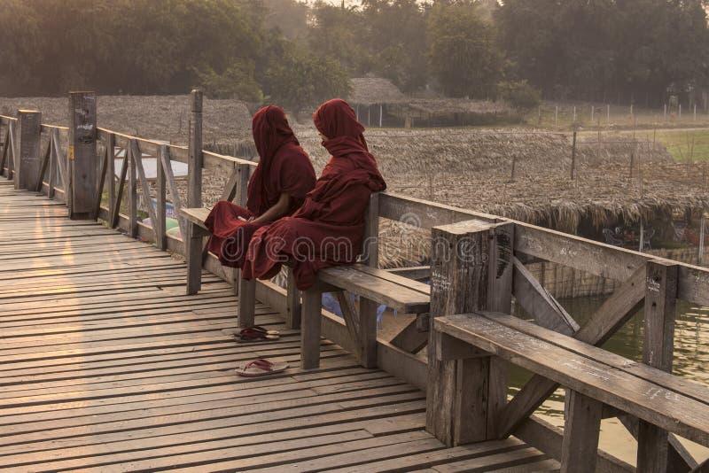 安装在U Bein桥梁的两名缅甸修士 免版税库存图片
