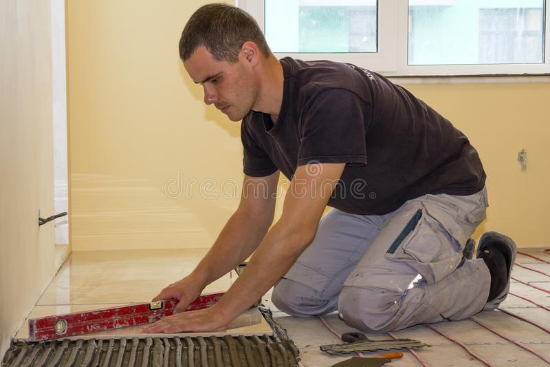 安装地垫的工作者 陶瓷砖和工具为铺磁砖工 库存图片