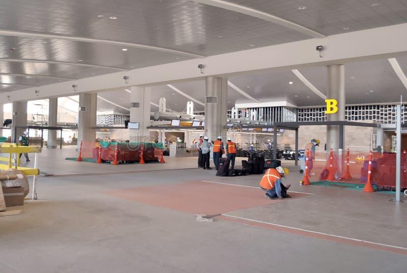安装地板的工作者在机场的建筑 免版税库存照片