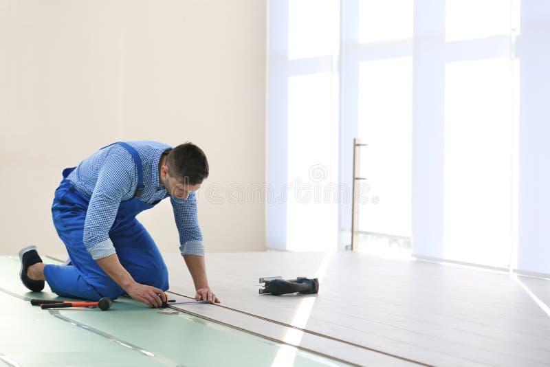 安装地板的男性工作者 免版税库存图片