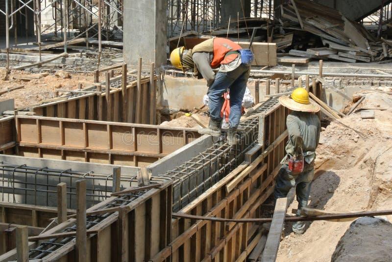 安装地梁模板的两名建筑工人 免版税库存图片